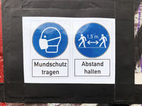 wear face mask and keep distance sign with (german: Mundschutz tragen - Abstand halten )