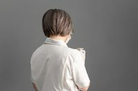 Rear view of female doctor in white coat using digital tablet standing back on gray background. Copy space