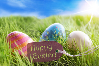 Three Colorful Easter Eggs On Sunny Green Grass With Label Happy Easter