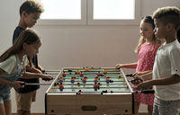 Group of multicultural children playing foosball