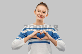 smiling teenage girl making hand heart