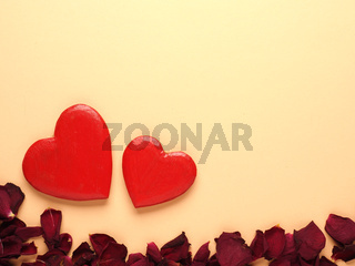 Rustic wooden hearts with rose petals on yellow background