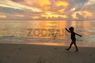 Toddler boy walking on beach at sunset