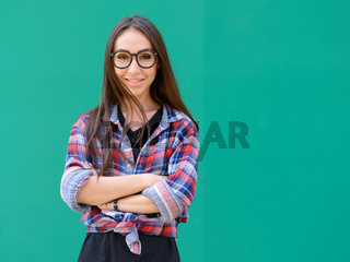 Portrait of young beautiful hipster woman with eyeglasses against blue background