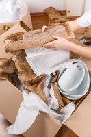Detail of woman packaging fragile items using crumpled packing paper. Concept of moving in or out.