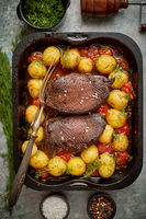 Delicious roasted goose breast served with vegetables, potatoes. Placed in metal baking dish