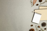Notebooks with dry leaves, pine cones on gray background. flat lay, top view, copy space. Work and study place. Autumn and winter concept