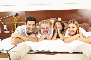 Glückliche Familie liegt gemeinsam auf Bett