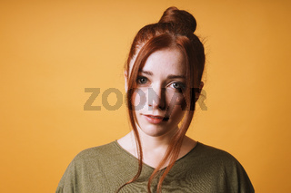 cool young woman with red hair messy bun hairstyle and loose strands