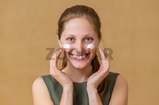 Happy woman applying white cream on her face and looking into camera.