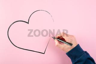 hand drawing heart shape using felt tip pen on pink background