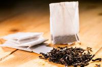 Tea bag on wooden background.
