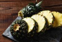 High angle shot of a fresh cut pineapple on wood and gray slate.