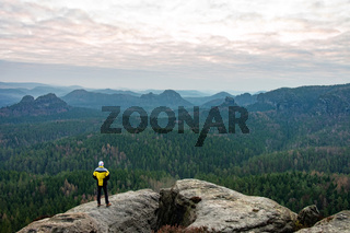 Silhouette of photographer standing on the rocky mountain