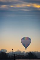 hot air balloon that furs the sky during a clear sunrise