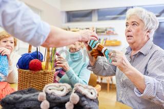 Seniorin lernt häkeln oder stricken in einem Handarbeit Kurs im Altersheim