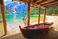 Wooden boat under boats house on Braies lake in alpine landscape