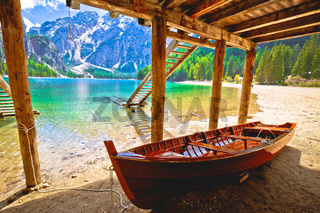 Wooden boat under boats house on Braies lake in alpine landscape