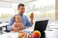 father with baby working on laptop at home office