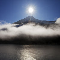 Sun over the mountain Standartindur with clouds at the fjord Seydisfjoerdur, Iceland, Europe