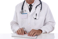 Doctor wearing a lab coat sitting at his desk typing on a computer keyboard. Isolated on white.