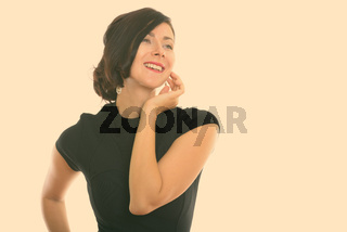Studio shot of young happy businesswoman smiling and thinking while touching her face