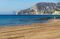 Sand beach with view on rocky cliffs in Calpe, Costa Blanca, Spain