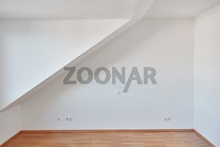 Wand mit Dachschräge im leeren Raum von Dachgeschosswohnung