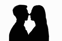 Two people in a counterlight touched each other with their noses