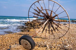 Abandoned beach umbrella on a rocky beach set against the sea.