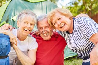 Drei lachende Senioren auf dem Campingplatz