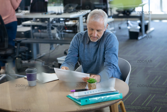 Senior businessman looking at documents at office