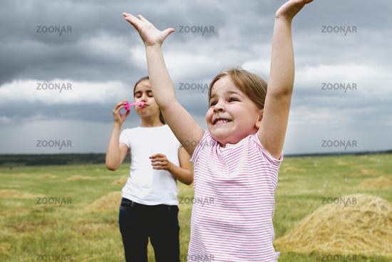 Kids having fun with soap bubbles in field