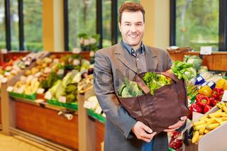 Mann beim Einkauf von Gemüse im Supermarkt