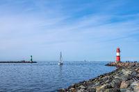 Mole mit Segelboot an der Küste der Ostsee in Warnemünde