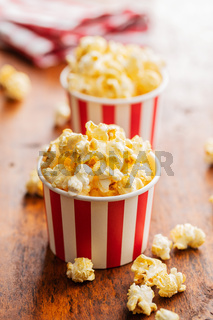Sweet tasty popcorn in striped paper cup.