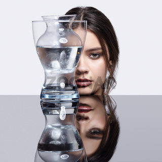 Girl hides her face behind a glass vase. Beauty portrait of young woman at the mirror table.
