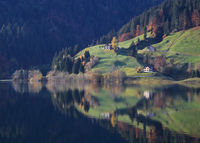 Colorful forest, green meadow an houses reflecting in Lake Wagital.