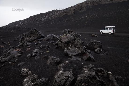 White car in black lava landscape, Landmannaleid, Krókagiljabrún, near Hekla, Iceland, Europe