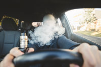 Vaping flavored e-liquid from an electronic cigarette in a car