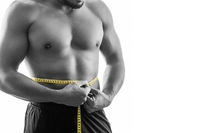 Young muscular shirtless man with beard measuring waist circumference, monochrome, isolated on white background. Workout, fitness, competition concept.