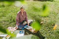 Female artist drawing flowers with oil paints outdoors