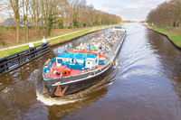 Cargo ship sails with recyclable metal on river