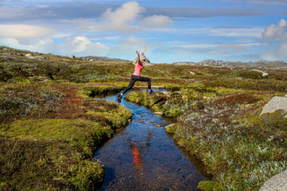 Woman run free jumping little meandering stream in high country