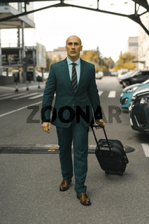 Businessman goes ahead holding suitcase in hand. Handsome Caucasian man walking past hotel parked cars. Business trip concept