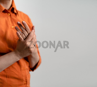 Mature Caucasian woman in orange shirts cares for hands skin. Female hands, close up shot. Square template with text space for publication on social networks
