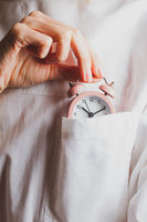 Woman puts a small alarm clock in her breast pocket