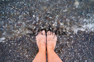 Top view of feet at the beach with sea waves. Grounding concept. connecting to nature