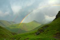 Green pure beauty of Alpine meadows and double rainbow