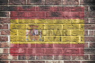 Spain flag on a brick wall background